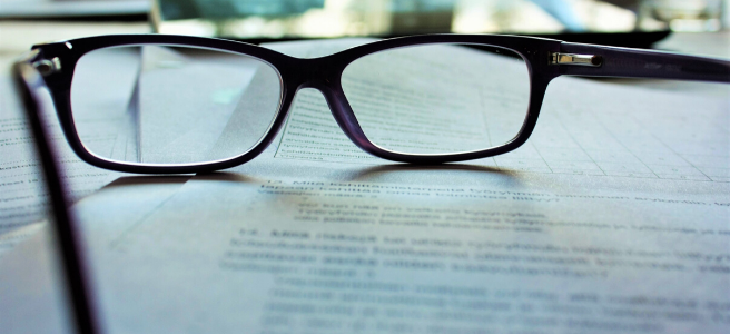 Image shows a pair of glasses on top of some paper with typewritten text on it. Proofreading and editing requires an eye for detail.