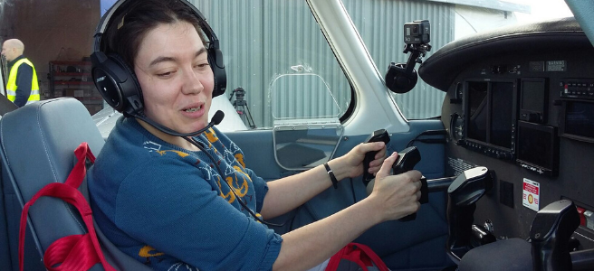 Image: Proofreader and editor Miranda K. Lloyd flying a plane.